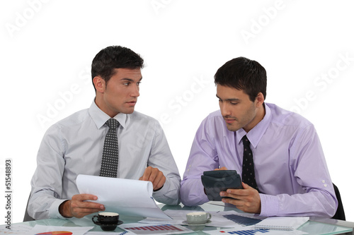 Two businessmen checking calculations