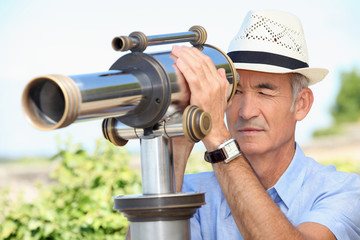 Senior man looking through a telescope