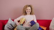 Young smiling girl with shopping bags sitting on the sofa