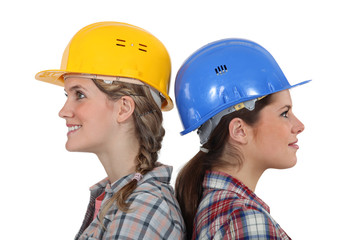 Two female builders standing back to back