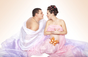 Happy Pregnant couple woman with man in studio