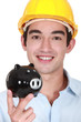 Builder holding piggy-bank