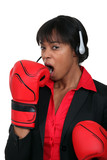 A black businesswoman yawning with boxing gloves on.