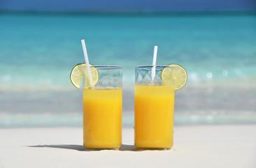 Two glasses of orange juice on the sandy beach