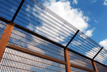 Security fence against blue sky