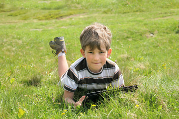 Boy with tablet PC on green grass