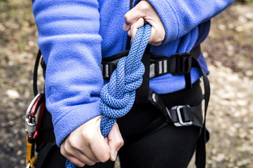 female hands holding a climbing rope with a secure node