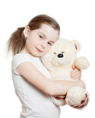 The pretty little girl embraces a teddy bear