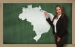 Teacher showing map of brazil on blackboard