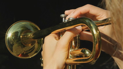 Female musician playing a trumpet. POV.