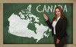 Teacher showing map of canada on blackboard