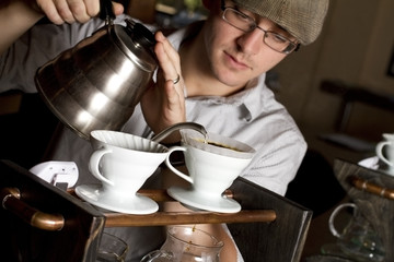 a coffee house employee brew a single cup of coffee