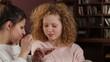 Two young women applying makeup, tracking shot