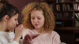Two young women applying makeup, tracking shot