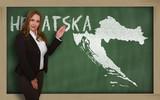 Teacher showing map of croatia on blackboard