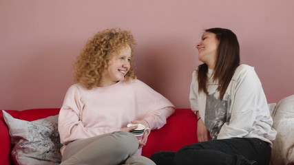 Two female friends sitting on the sofa and chatting