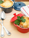 French Onion Soup Gratin in red and blue pots on table top