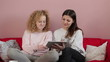 Two female friends sitting on the sofa with tablet computer