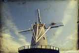 Vintage photo of dutch windmill over blue sky