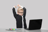 Angry schoolboy raises his fists threateningly at laptop
