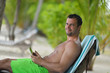 man ralaxing and use tablet at beach