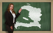 Teacher showing map of haiti on blackboard
