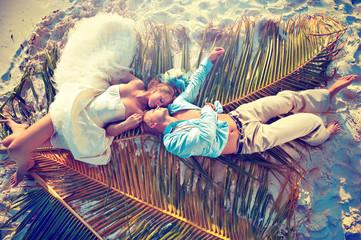 Wedding couple lying on palm leaf