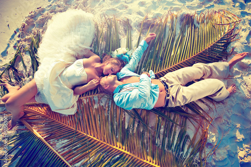 Wedding couple lying on palm leaf