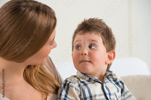 Happy mother talking to her son at home