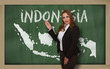 Teacher showing map of indonesia on blackboard