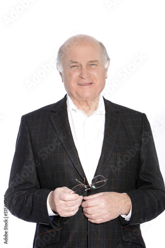 Smiling pensioner holding his glasses