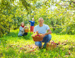 family with  harvested apples in garden