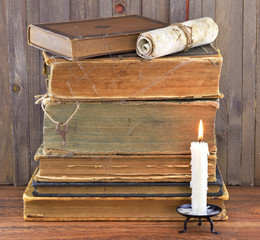 Old stacked books with candle