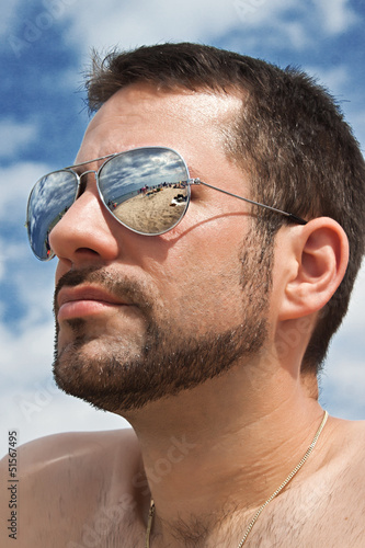 man with silver mirror sunglasses on the beach