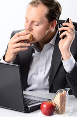 Hardworking man taking a bite of his sandwich while working