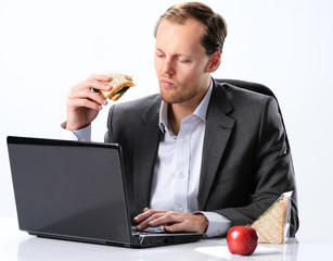 Hardworking man eating at his desk through lunch break hour
