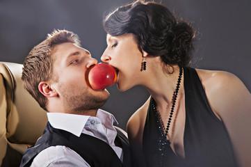 парень и девушка кусают одно яблоко