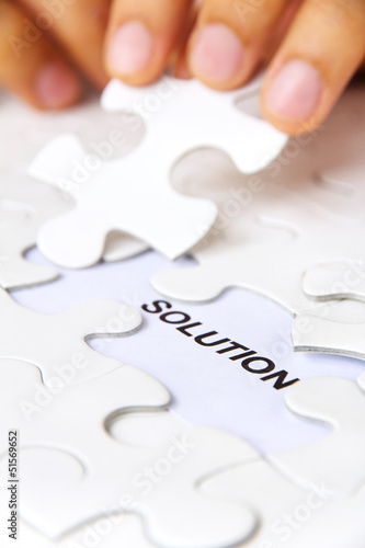 hand holding a puzzle piece, solution concept