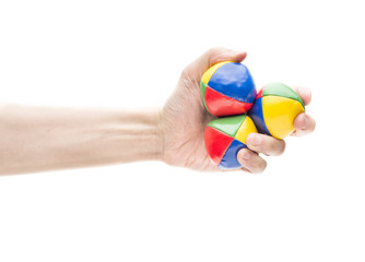 Hand holding three juggling balls