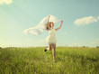 The young beautiful girl in a white dress enjoys a wind, the sun