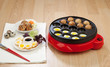 Takoyaki ball cooking machine display with takoyaki and fried eg