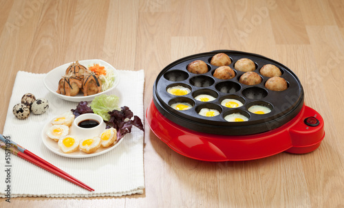 Takoyaki ball cooking machine display with takoyaki and fried eg