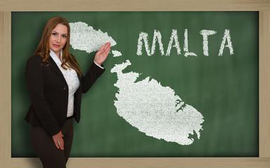 Teacher showing map of malta on blackboard