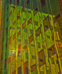 Office building with green yellow reflexions in windows