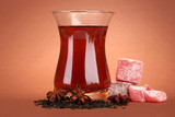 glass of Turkish tea and rahat Delight, on brown background