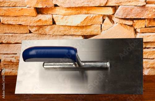 Metal tool for building on brick wall background