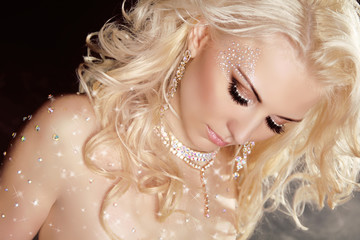 Closeup of blond sexy girl model wearing in twinkled crystals wi