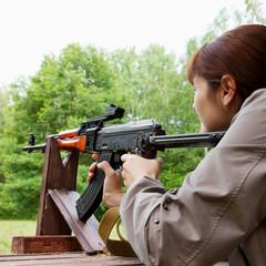young woman shooting an automatic rifle for strikeball