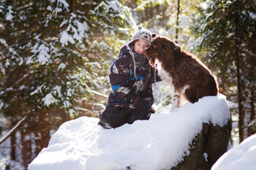 young boy playing out in the snow with his pet dog