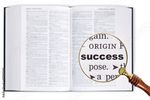 Success through a magnifying glass over Dictionary.